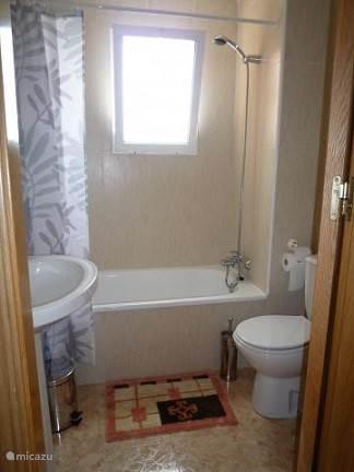 De badkamer heeft een ligbad met douche en achter de deur is er een rekje voor uw toiletgerief.