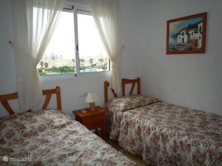 De tweede slaapkamer heeft twee éénpersoons bedden en ook een linnenkast  en grote spiegel.