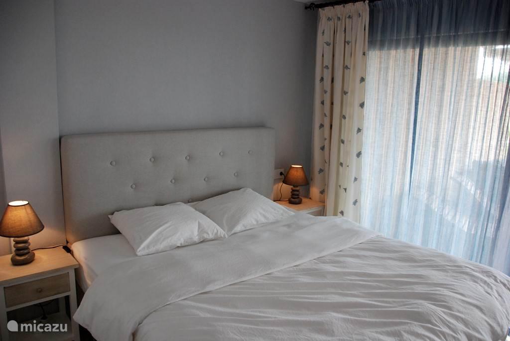 Grote slaapkamer en suite met schuifdeuren naar terras.