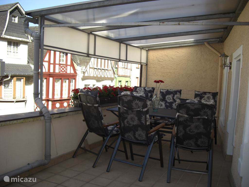 Spacious balcony with covered area and look at beautiful half-timbered houses.