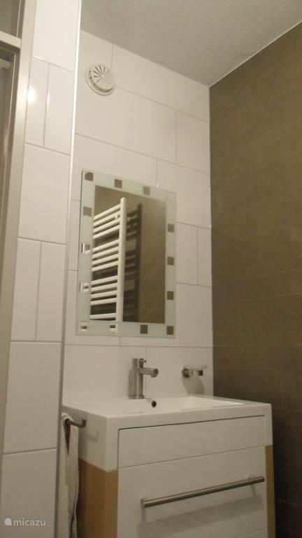 Moderne wastafel in ruime badkamer, voorzien van designradiator en praktische opbergruimte. Uitgeslapen, dan heerlijk 's morgens je zelf opfrissen en weer klaar maken voor de onvergetelijke vakantiedagen.