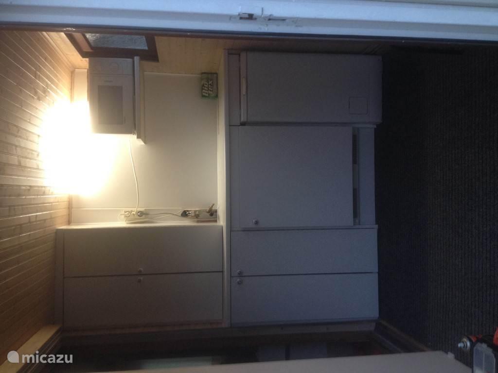 De hal met in de kasten de CV, een koelkast en een wasmachine. Op de plank staat een magnetron.