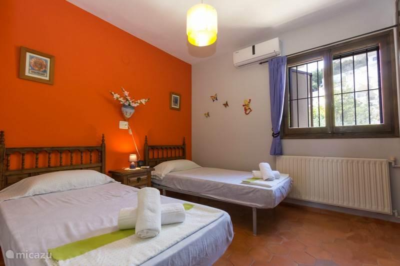 Slaapkamer met twee single bedden en airco
