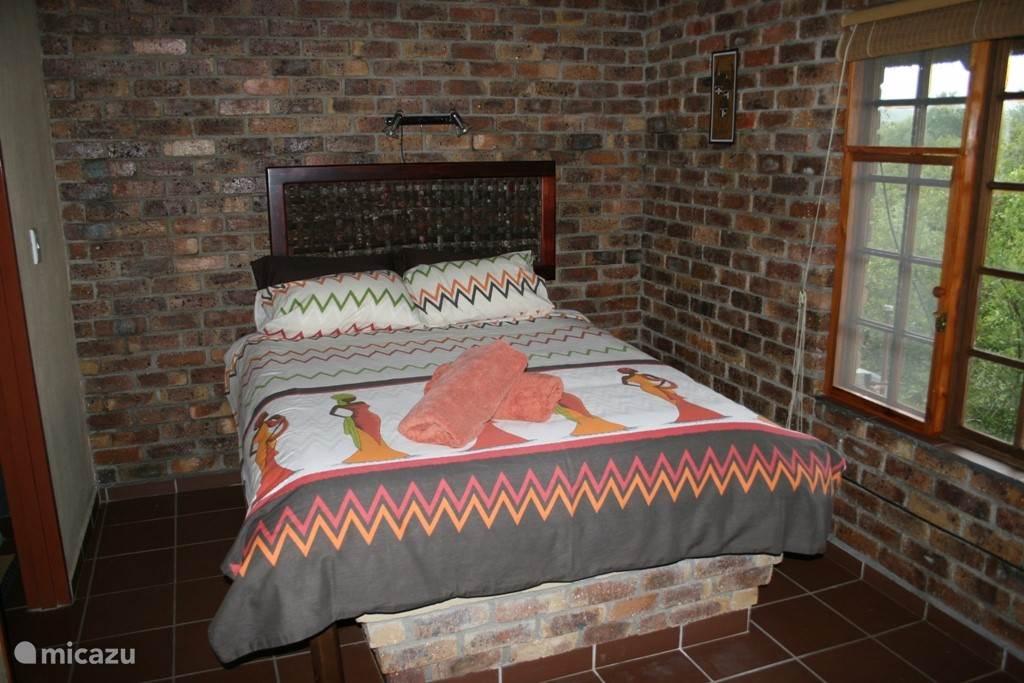 De slaapkamer in de cottage voorzien een fan en airco.