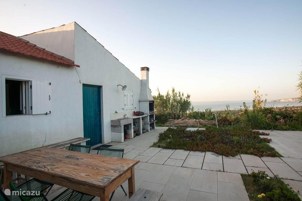 Het terras achter het huis, met een spectaculair uitzicht over de zee.