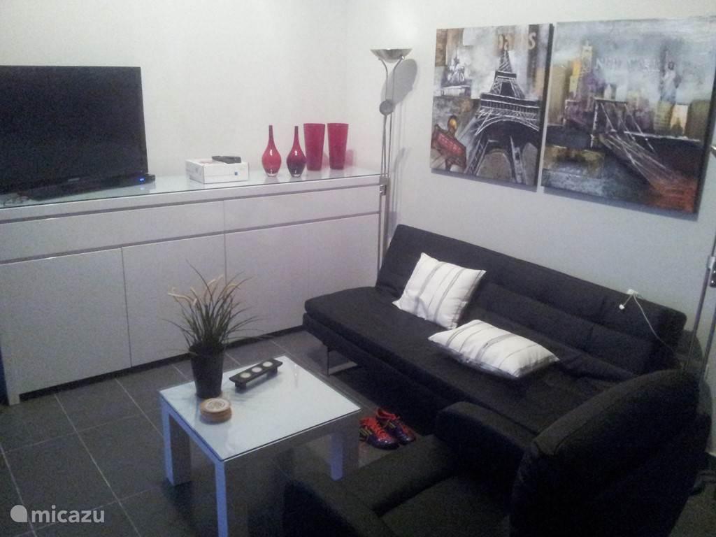 Het zitgedeelte bestaat uit een (lig)bank + enkele relax-fauteuils. Verder is een breedbeeld-tv aanwezig met Canal Digitaal. Er is in deze ruime woonkamer een airco/verwarming, die zowel in de zomer als de winter voor een aangename temperatuur zorgt.