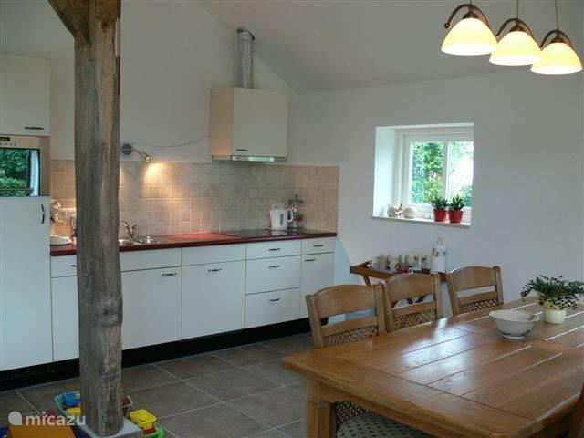 Keuken met kookplaat, vaatwasser en magnetron.