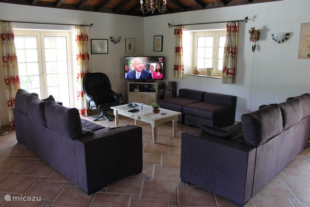 De zithoek bij de tv/ muziekinstallatie met direct toegang naar de veranda aan de westkant en het terras aan de noordkant.