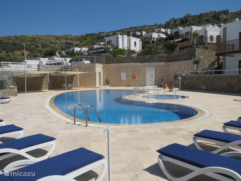 Het rustige zwembad op circa 70 meter van Villa Beraber met ligbedden, zitjes en zonnedoek. Ook bad voor de allerkleinsten.
