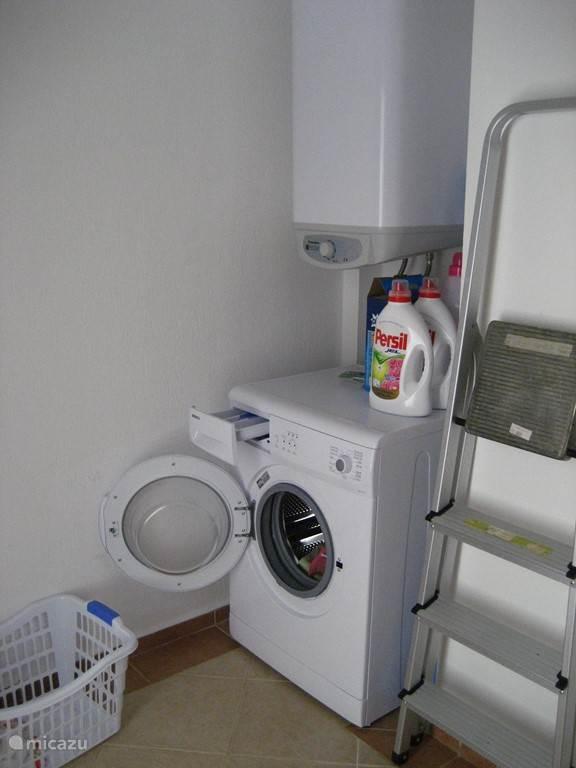 Bijkeuken met wasmachine en boiler.