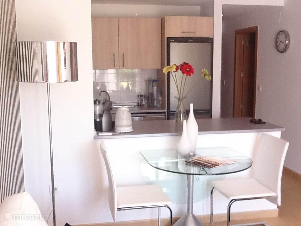 De eettafel ( kan uitgeschoven worden en heeft nog twee extra witte stoelen ) en zicht op de open keuken.