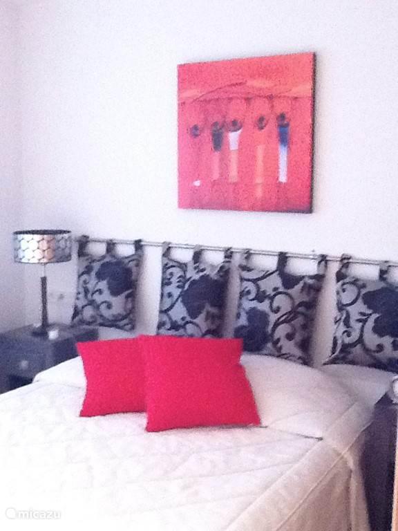 Slaapkamer met twee-persoonsbed, nachtkastjes met lampen, Panasonic airco en vaste kledingkast. Er is een schuifpui met toegang tot het terras aan de achterkant van het appartement.