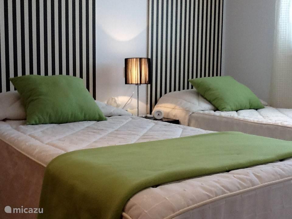 Slaapkamer met twee 1-persoonsbedden, nachtkastje met lamp, schuiframen, Panasonic airco en vaste kledingkast.