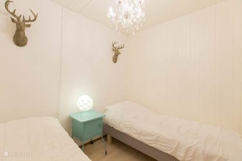 Slaapkamer met twee eenpersoonsbedden die ook aan elkaar geschoven kunnen worden.