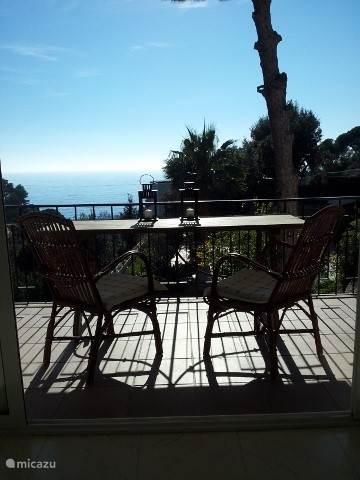 Het terras aan de woonkamer met uitzicht op zee en bos (foto in januari gemaakt).