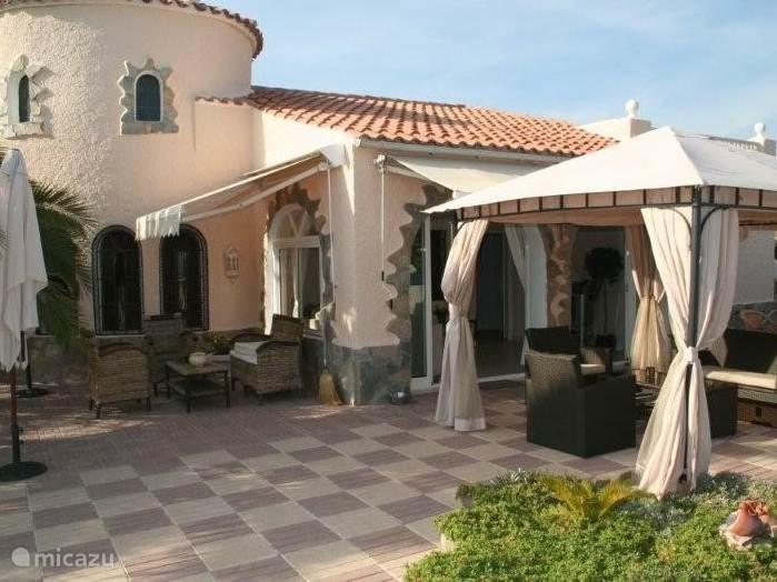 Overkapt veranda met eet- en relaxgedeelte.