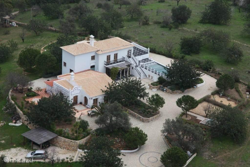 Zuidkant van het huis, links de Capela en Quinta, rechts de Fazenda met groot boventerras en zwembad met uitzicht op zee. De cour (voorplein) is gedeeltelijk overdekt, grenzend aan de keuken, met lange tafel(s) en zitplaatsen voor 10 personen. Hier staat ook de (gas) bbq.
