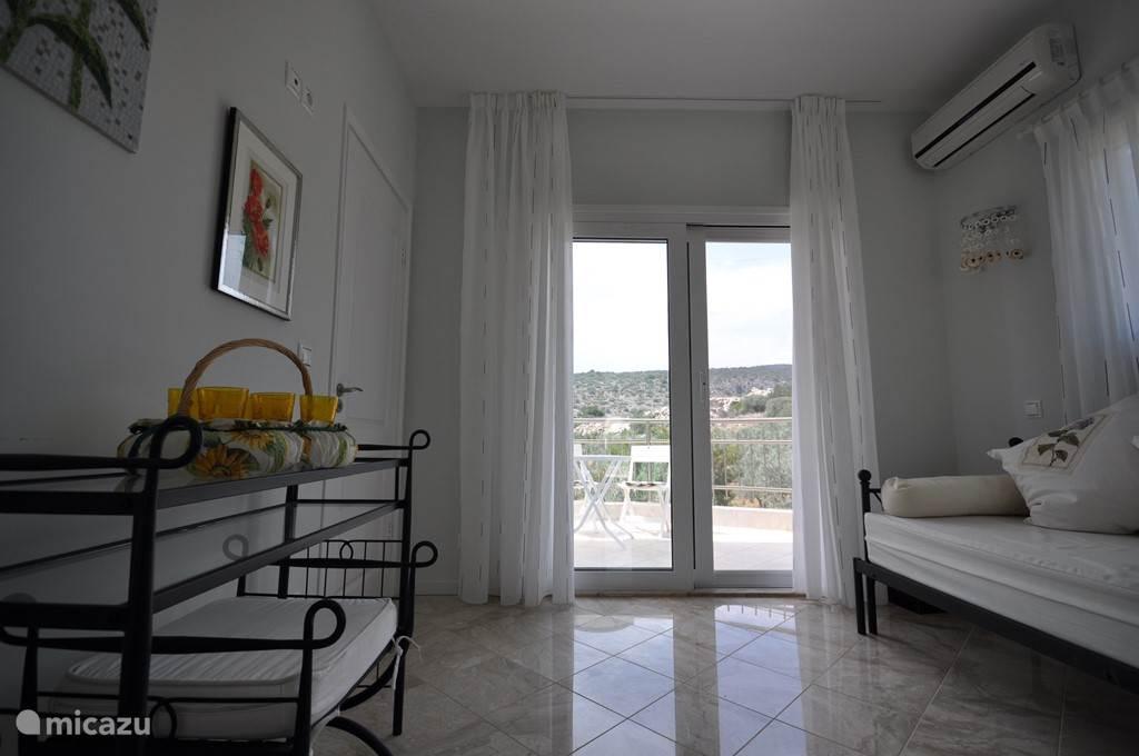 Slaapkamer Sacha bed uitschuifbaar tot tweepersoonsbed , schuifdeur naar eigen balkon met terrasset . zee en bergzicht