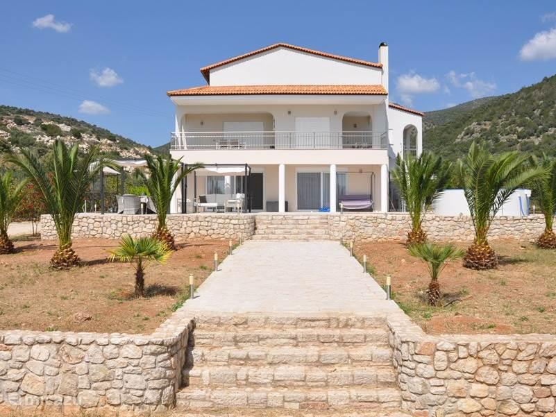 Zeer Luxe Villa Livadia.  vooraanzicht met palmboom tuin en in de achtergrond de bergen om heerlijk te wandelen.