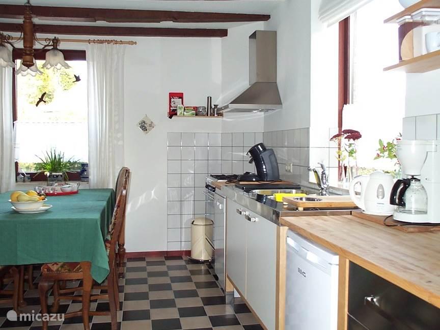 De ruime keuken met grote eettafel (te vergroten tot 8 zitplaatsen). Ook hier is de originele balkenlaag uit de vakwerkperiode zichtbaar.