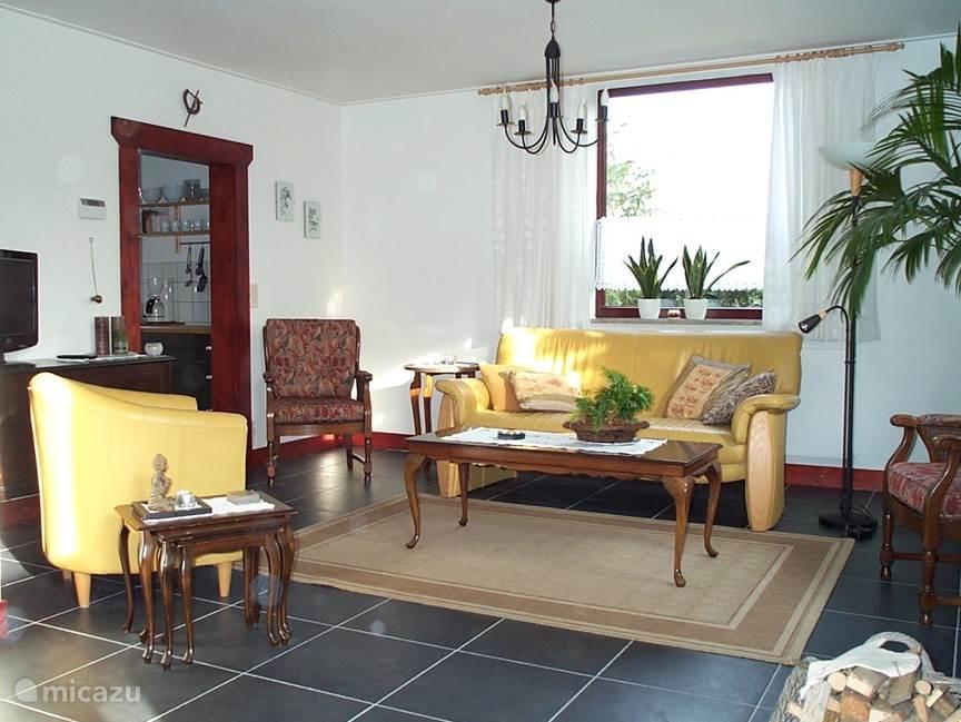 Vanuit de keuken komt u via de toegang (links op de foto) in de woonkamer. Dit is het deel waar de TV staat.