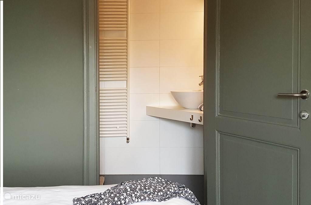De slaapkamers zijn uitgevoerd in zacht vergrijsde pasteltinten, en deze heeft ook nog een badkamer op de kamer.