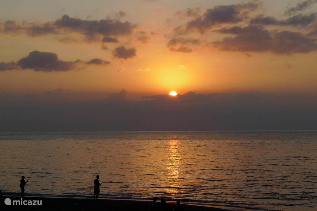 vissers op het strand bij ondergaande zon