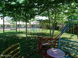 de speeltuin met glijbaan, draaimolen schommelstoel en klimrek