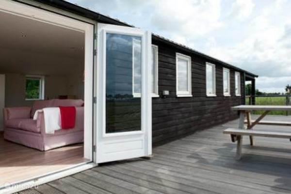 Openslaande deuren naar een groot privé terras. Er is tevens een overdekt terras aanwezig.
