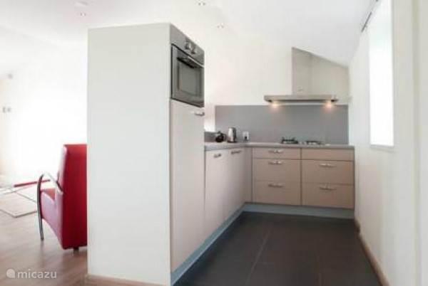 Complete keuken met inbouwvaatwasser, magnetron, oven en koelkast.