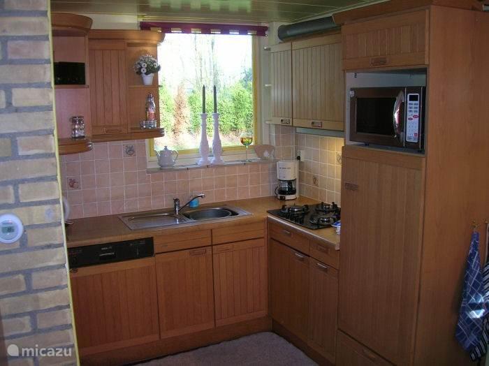 Keuken met o.a. vaatwasser, koelkast met vriesvakje en combi magnetron.