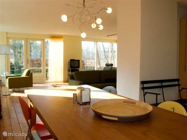 Ruime woonkamer met open keuken en landelijk uitzicht.