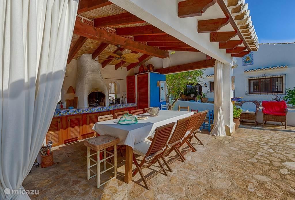 Volledig ingerichte buitenkeuken met tien stoelen en zicht op de tropische tuin