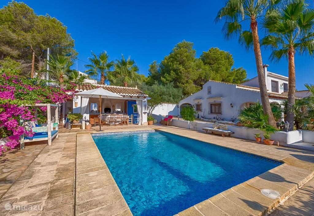 Ruim zwembad met romeinse trappen, veilig omringd door een muurtje met afsluitbaar hek, volledig ingerichte buitenkeuken en heerlijke warme buitendouche. Vanuit zwembad door de bomen zicht op de zee van moraira