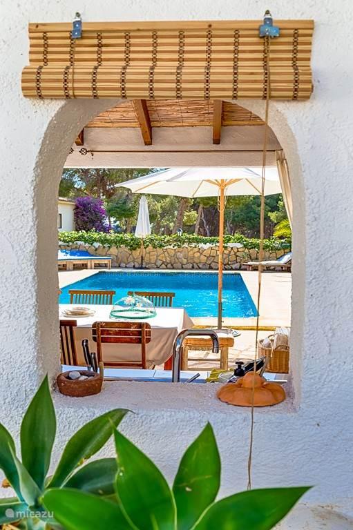 Entree vanaf de ingang waar je via de buitenkeuken naar het zwembad kijkt.