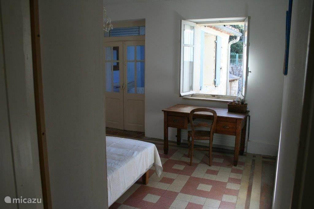 Slaapkamer 3 heeft twee eenpersoonsbedden, een kleine legkast en een groot bureau. Het raam, met luiken, geeft uitzicht op de binnentuin. De kamer is te bereiken via de keuken en staat via suitedeuren in verbinding met slaapkamer 4.