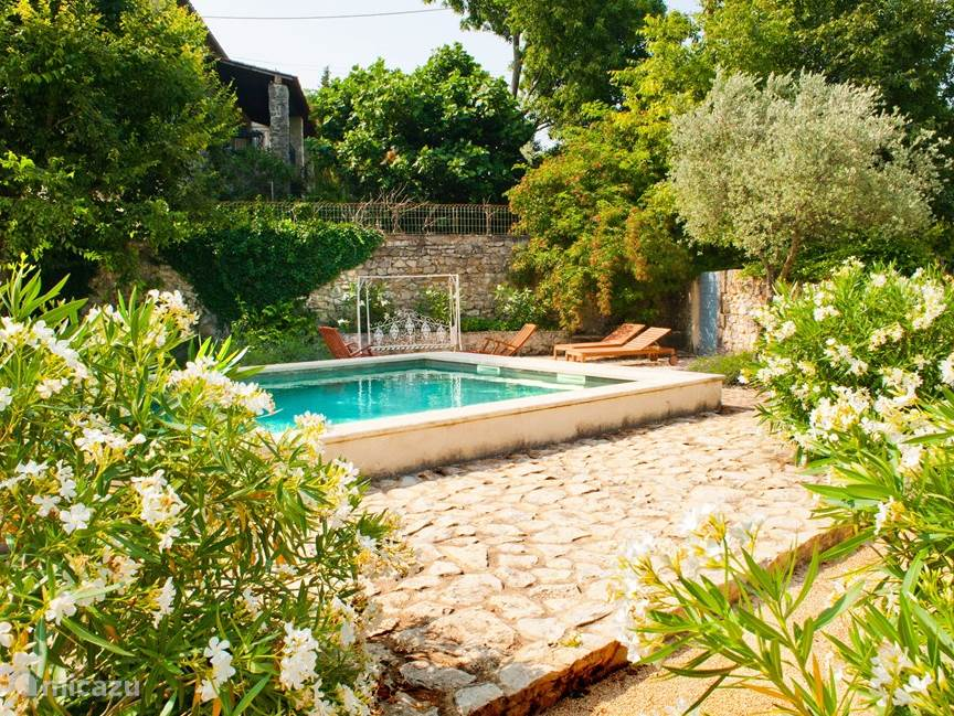 The walled courtyard consists of two parts: a lower lomme rich area with outdoor kitchen, bedroom and bathroom 6 and an upper portion which houses the pool and herb garden. Oleanders, lavender, olive trees, mulberry trees and olive trees give the garden a Mediterranean character.