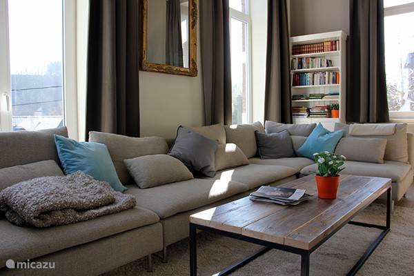 Gemütliches Wohnzimmer mit Sitzgelegenheiten für 9 Personen, die die Größe von 1900 mit modernem Interieur kombiniert