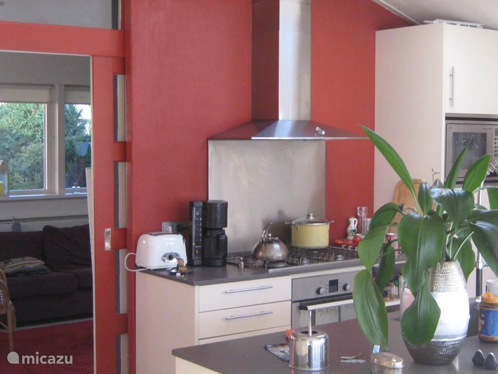 Open keuken met oven, combimagnetron, koelkast. De vriezer bevindt zich in de bijkeuken