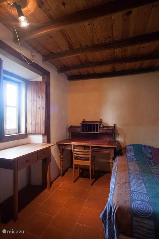 Deze slaapkamer met tweepersoonsbed grenst aan de woonkeuken