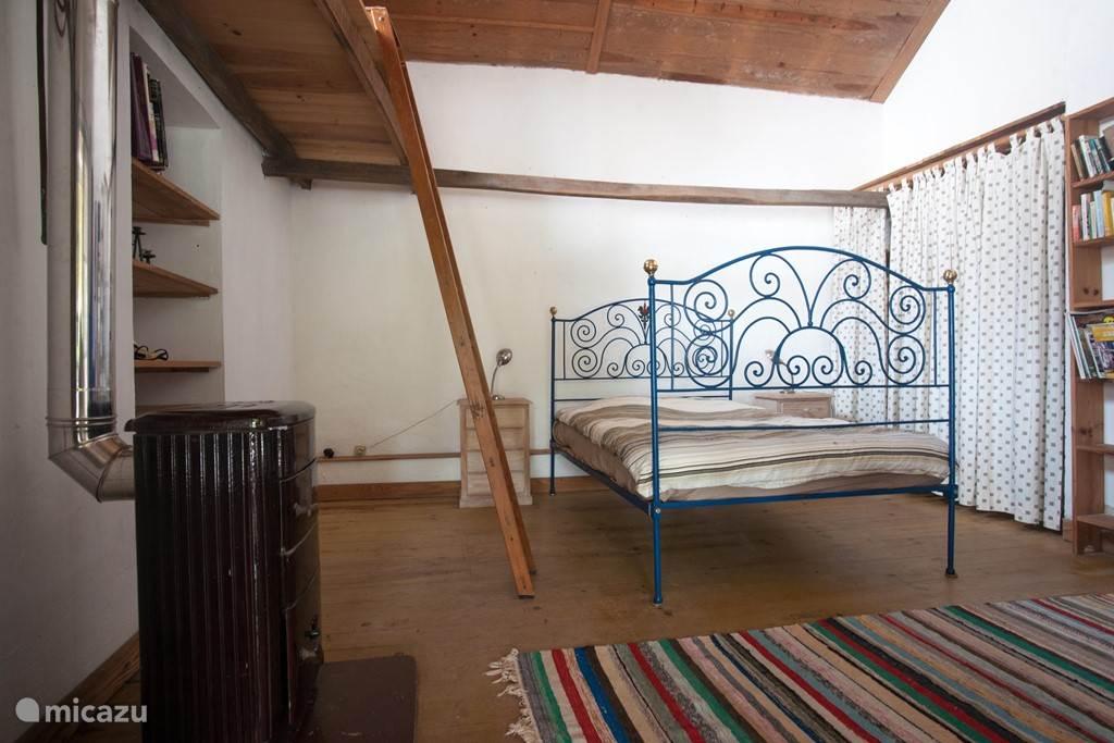 De tweede slaapkamer met een tweepersoonsbed. Vanuit deze kamer zijn er openslaande deuren naar het terras toe