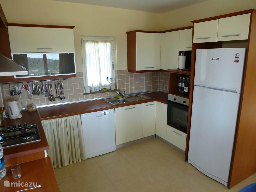 Keuken met vaatwasser, koelkast, oven en gasfornuis. Kuche