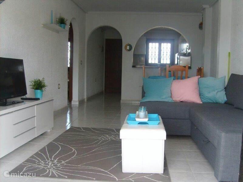 Huiskamer met keuken, slaapbank en flatscreen tv