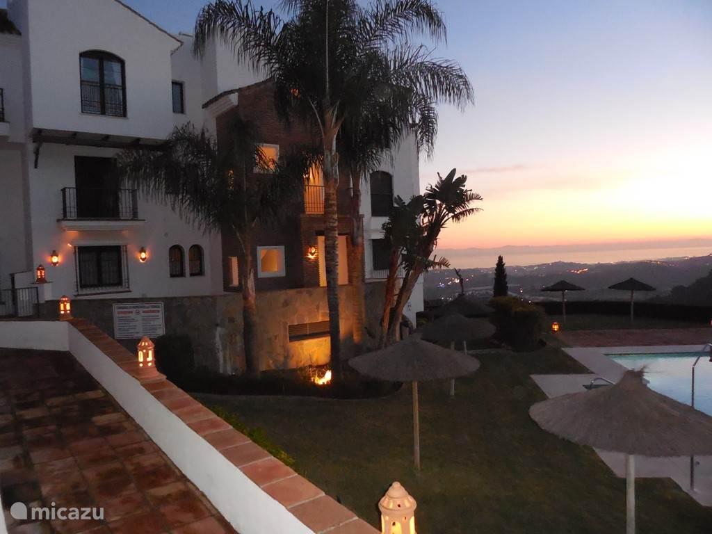 Uitzicht op zwembad is 's avonds sfeervol verlicht.
