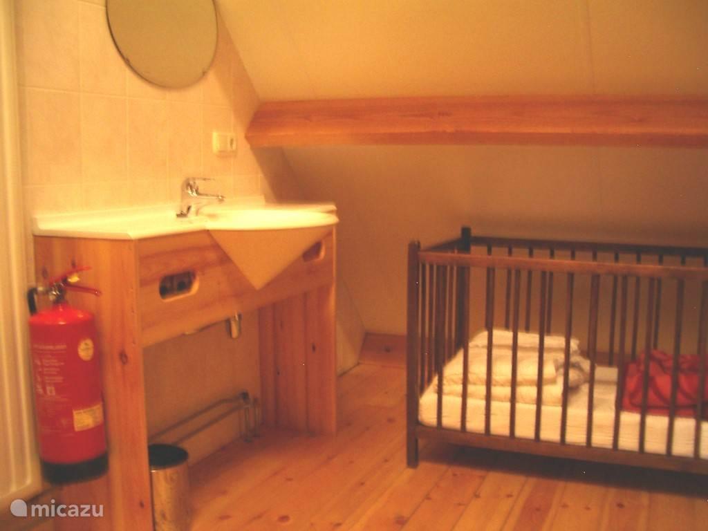 Een extra wastafel op de slaapzaal. Er is een kinderbed aanwezig.
