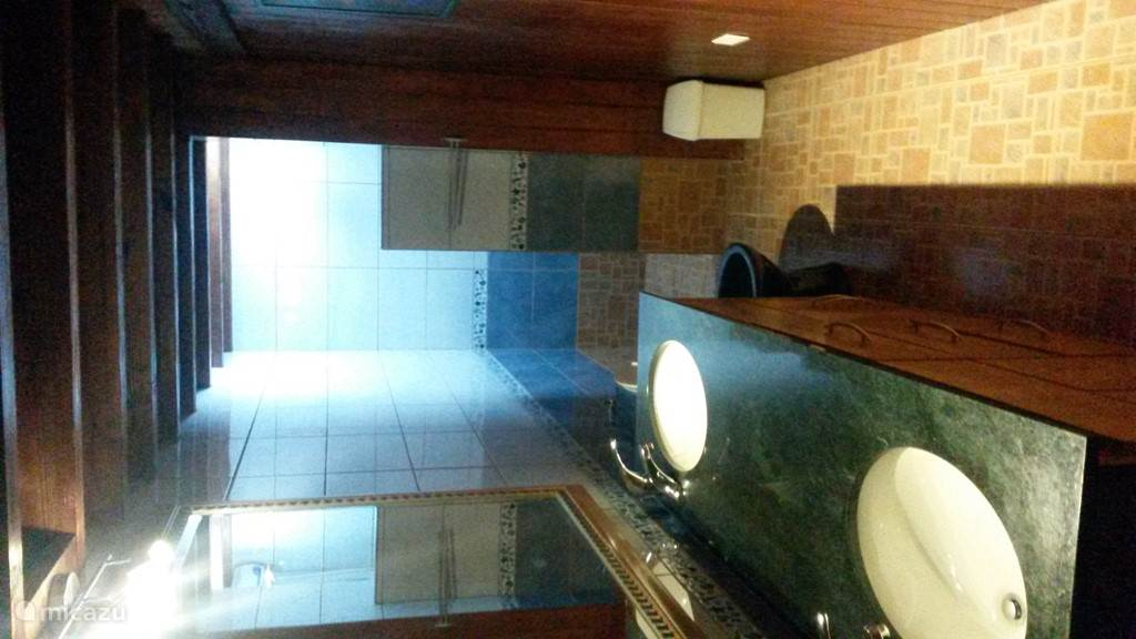The bathroom of the apartments. Large sink and rear shower with hot water supply.
