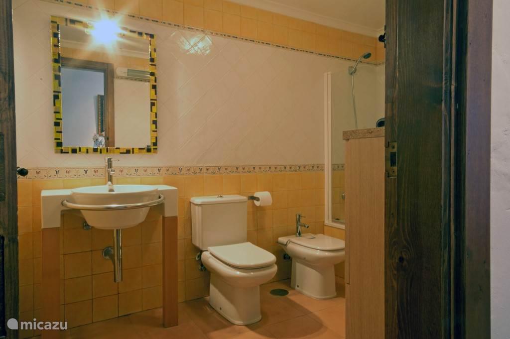 Badkamer begane grond met bad/douche combinatie.