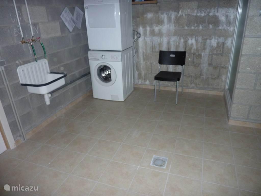 In de kelderruimte, de wasplaats met wasmachine, droogkast en een douche.