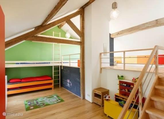 Een grote speelruimte voor de kinderen, met winkeltje, strips, speelgoed... Een slaapplaats voor 4 kinderen via de ladder of voor 2 à 3 volwassenen (éénpersoonbedden)