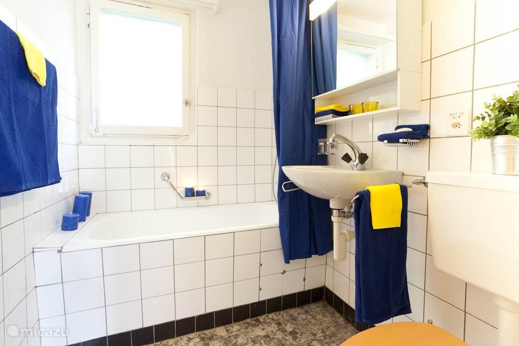 Badkamer met bad. Toilet en wastafel. Douchen kan in het bad.